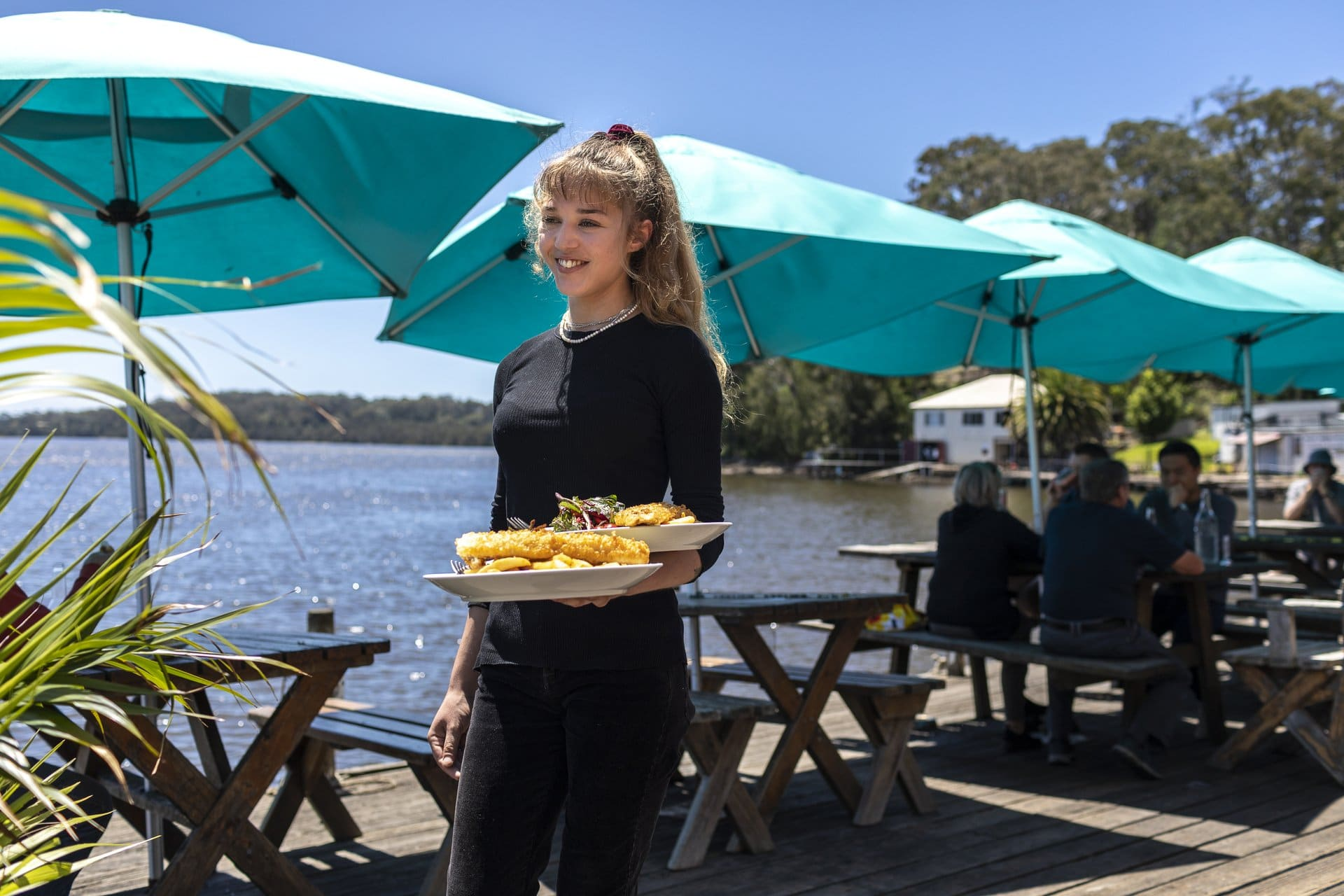 Waitress serving fish and chips at the Tuross Boatshed